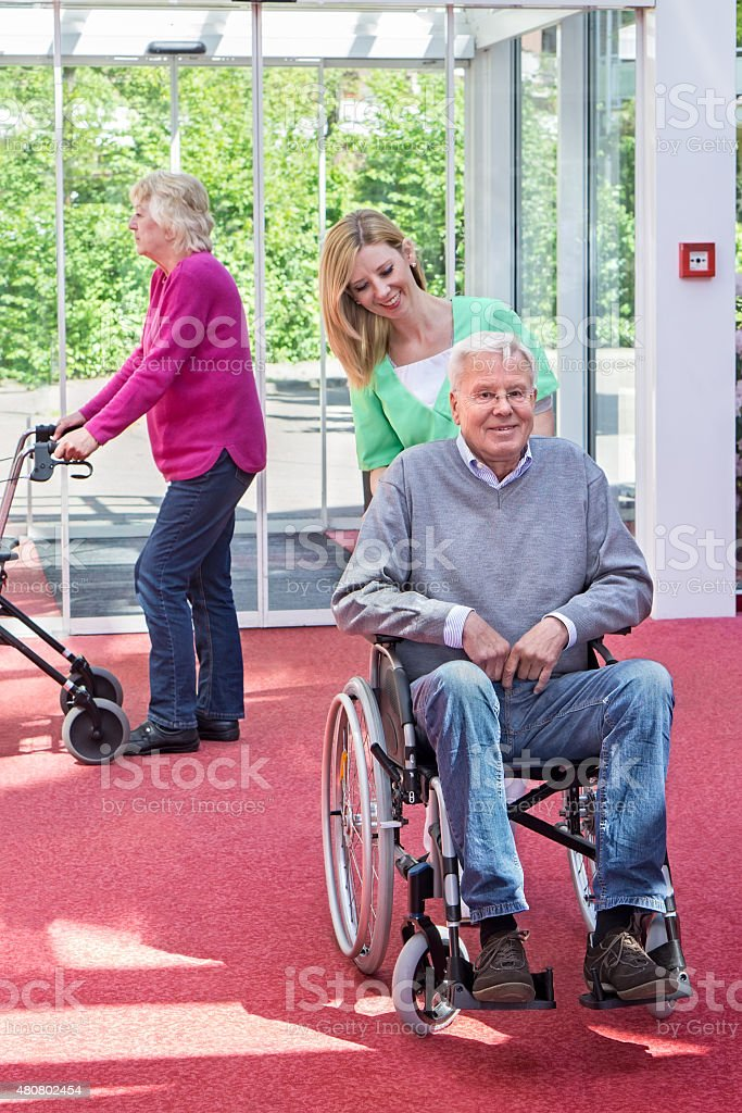 Nurse Pushing Senior Man in Wheelchair, Nursing Home Lobby. stock photo