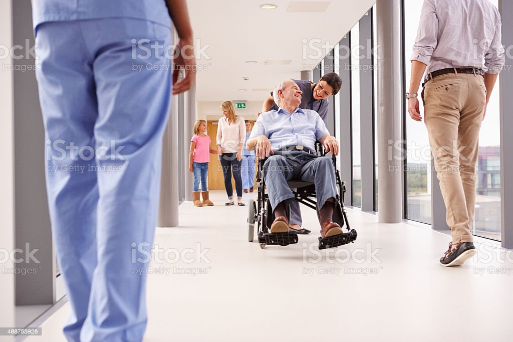 Nurse Pushing Senior Patient In Wheelchair Along Corridor stock photo