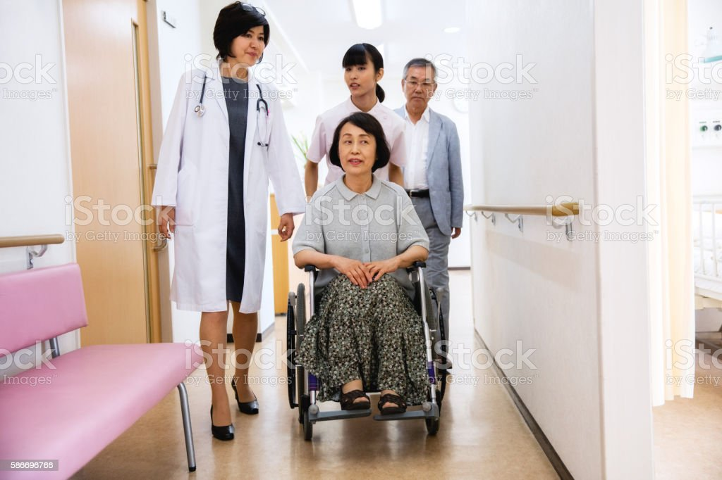 Nurse pushing senior woman sitting on wheelchair stock photo
