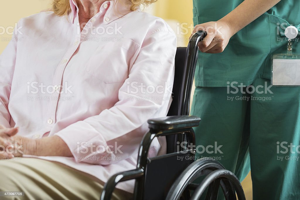 Nurse pusing elderly patient in wheelchair, focus on hands royalty-free stock photo