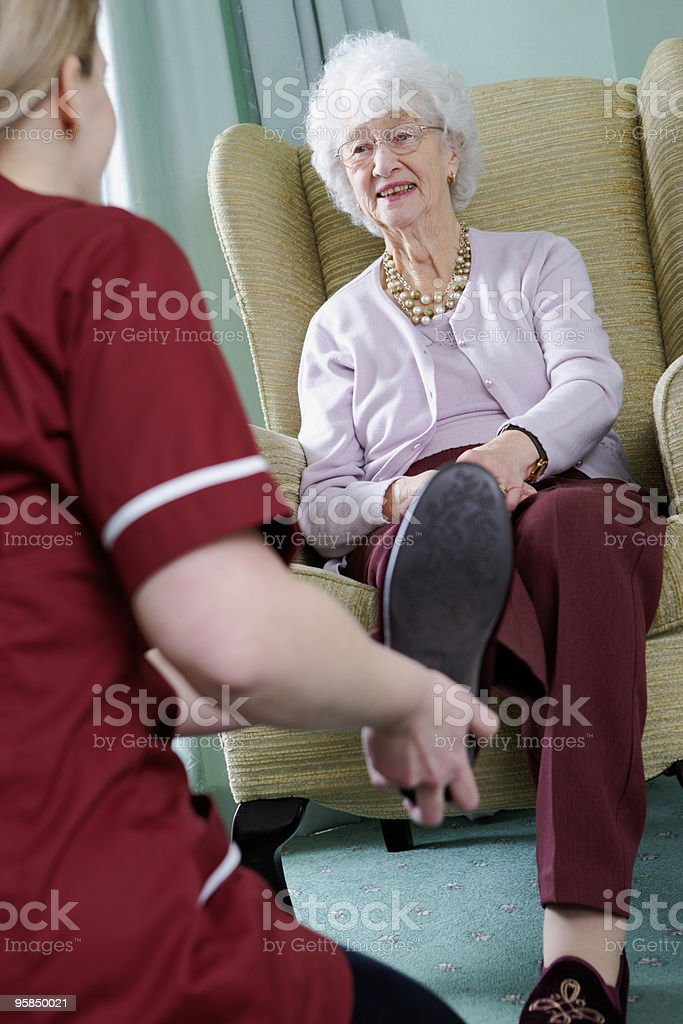 Nurse putting slippers on senior woman in a care home royalty-free stock photo