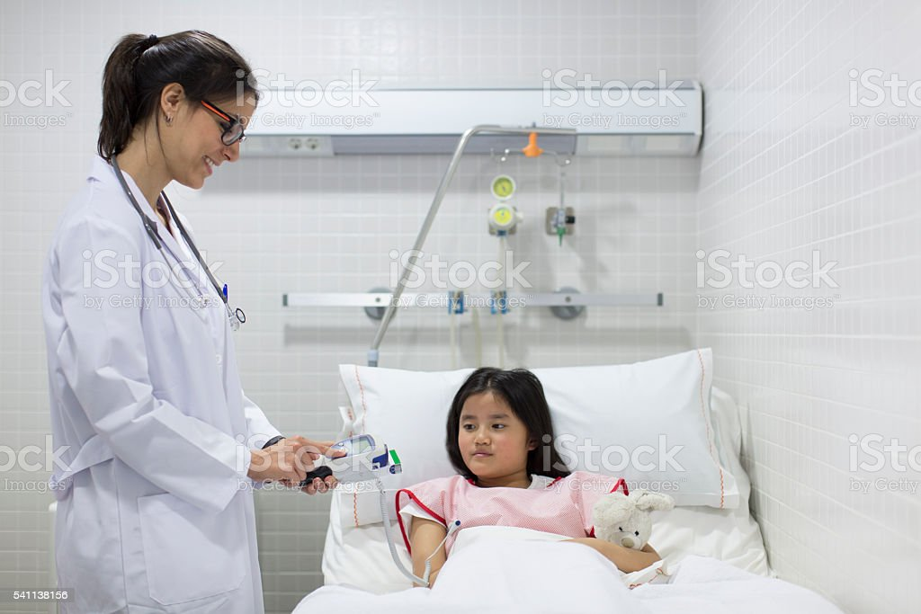 Nurse reading body temperature with electronic thermometer stock photo