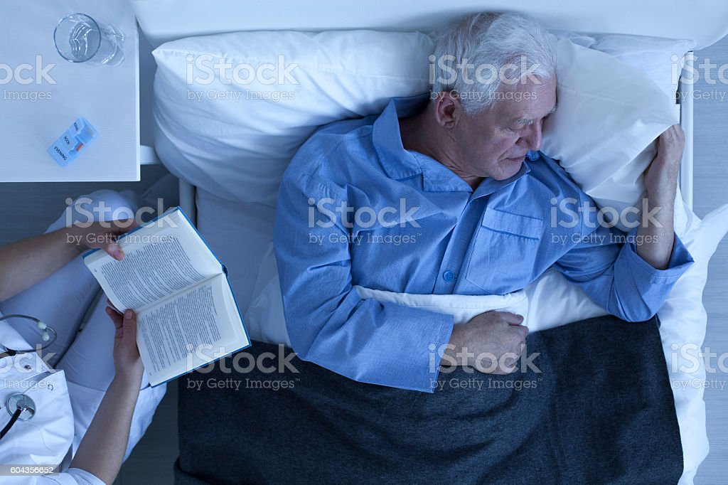 Nurse reading for senior patient stock photo