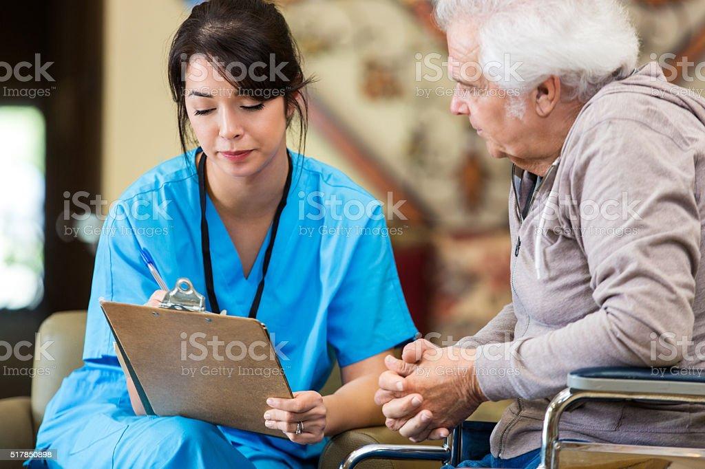 Nurse reveiws patient information with senior man stock photo