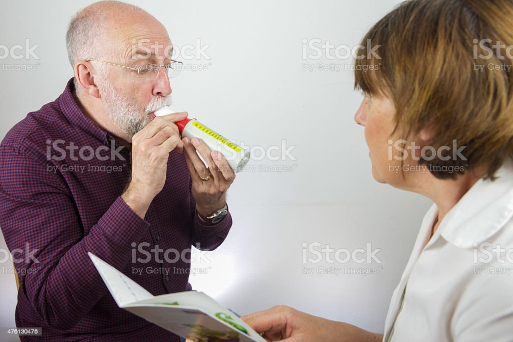 Nurse reviews patient's lung capacity with a peak flow meter stock photo