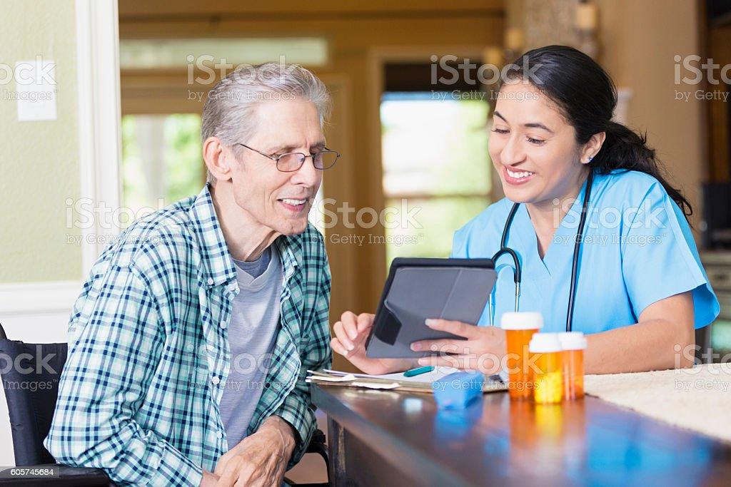 Nurse reviews senior patient's medical chart on digital tablet stock photo