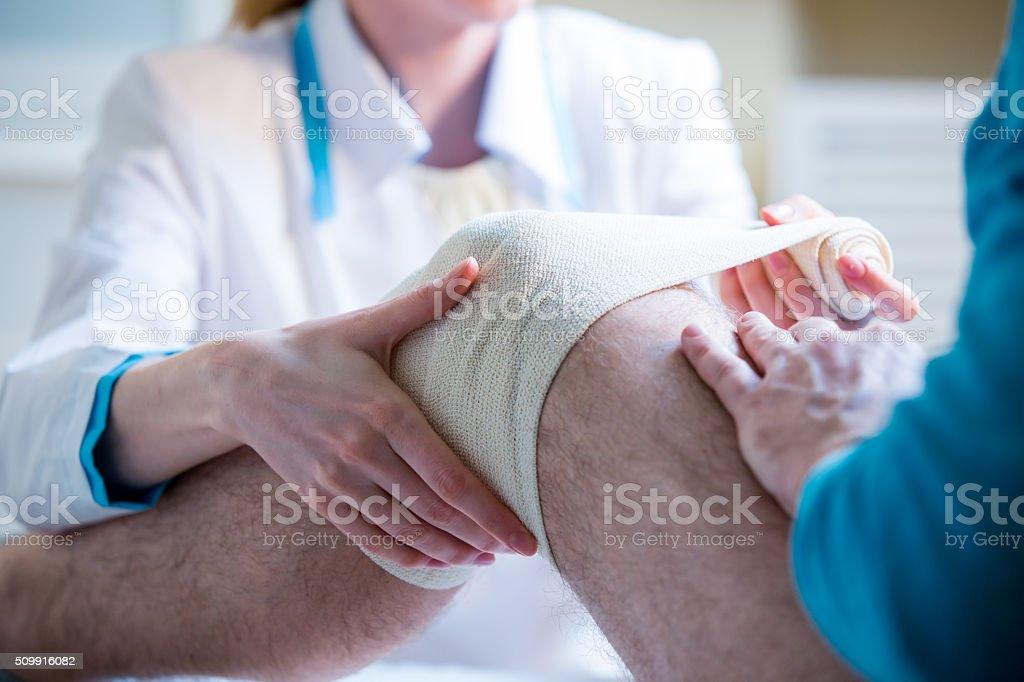 Nurse rewinding knee bandage stock photo