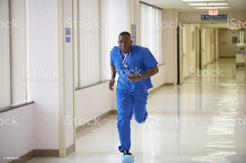 Nurse running through a hospital corridor stock photo