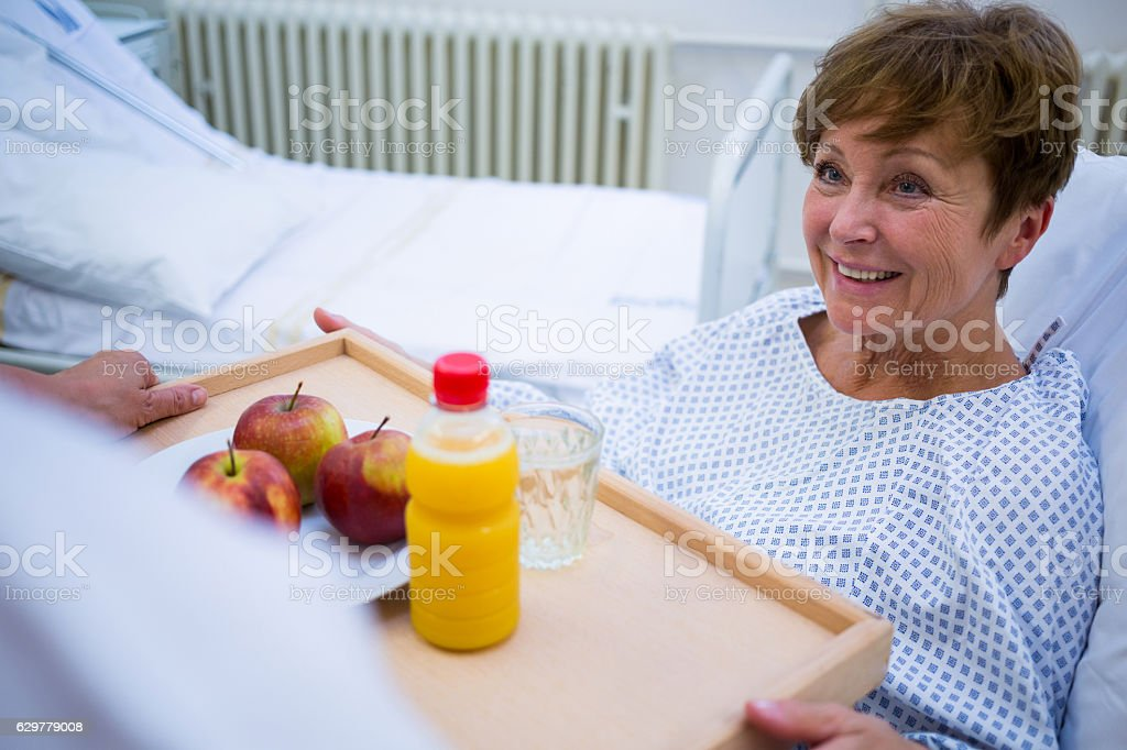 Nurse serving a breakfast to patient stock photo