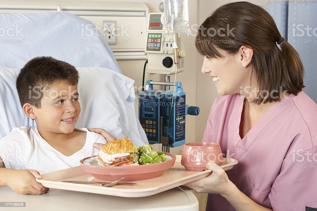 Nurse Serving Child Patient Meal In Hospital Bed stock photo