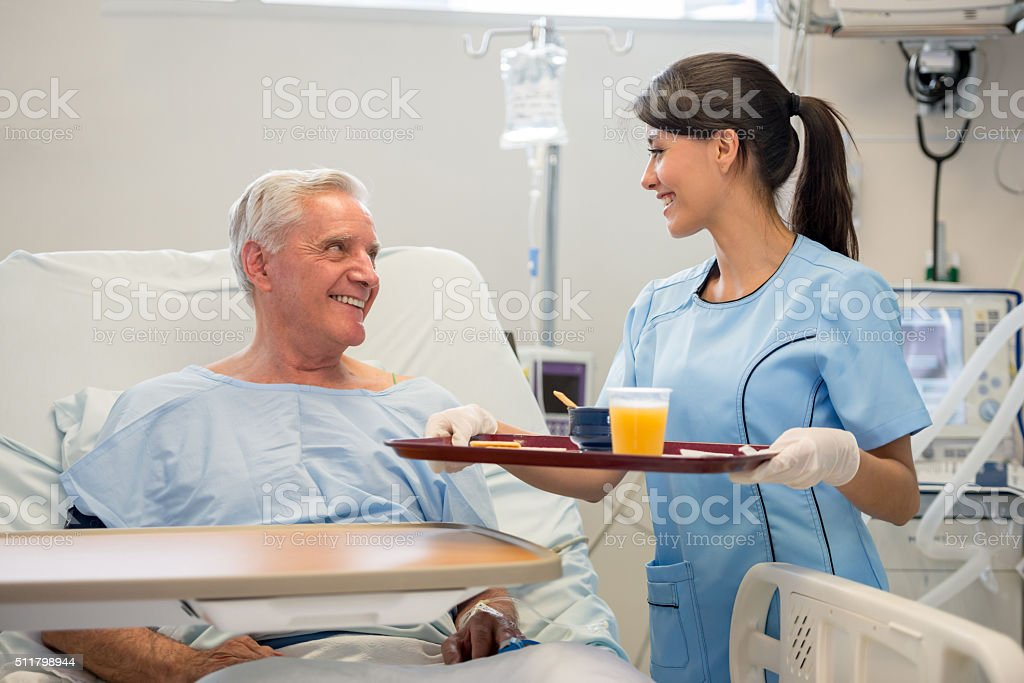 Nurse serving food to patient in the hospital stock photo