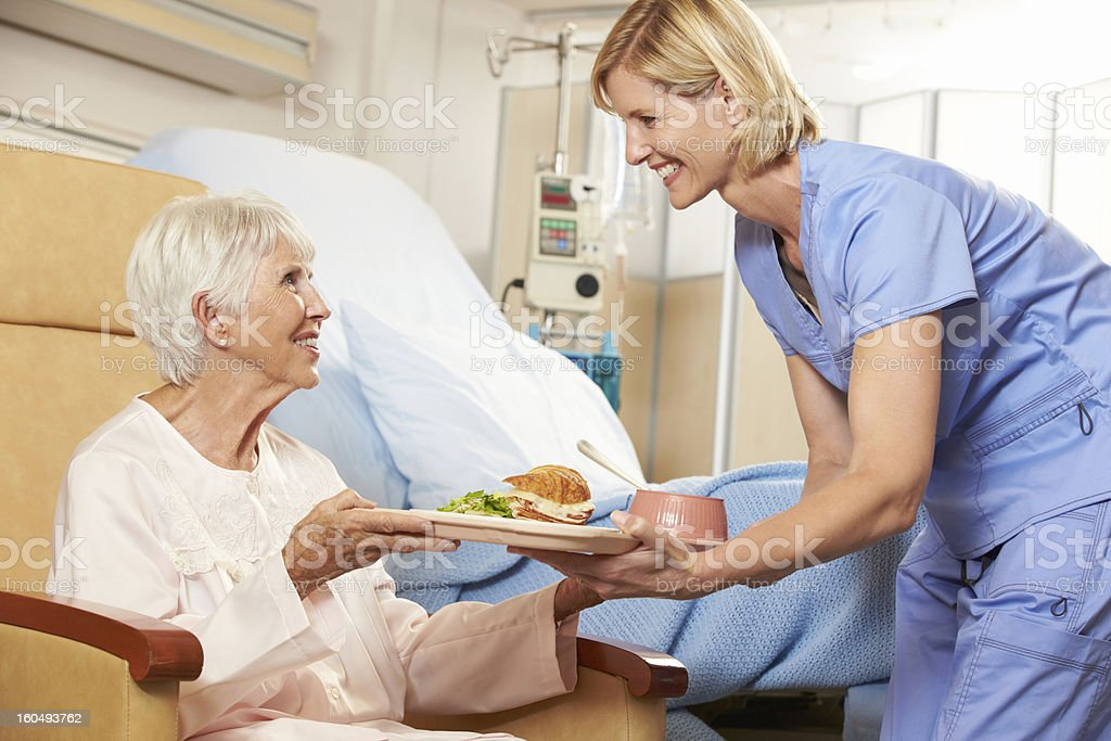 Nurse Serving Meal To Senior Female Patient Sitting In Chair stock photo