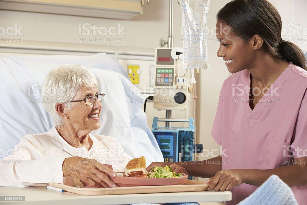 Nurse Serving Senior Female Patient Meal stock photo