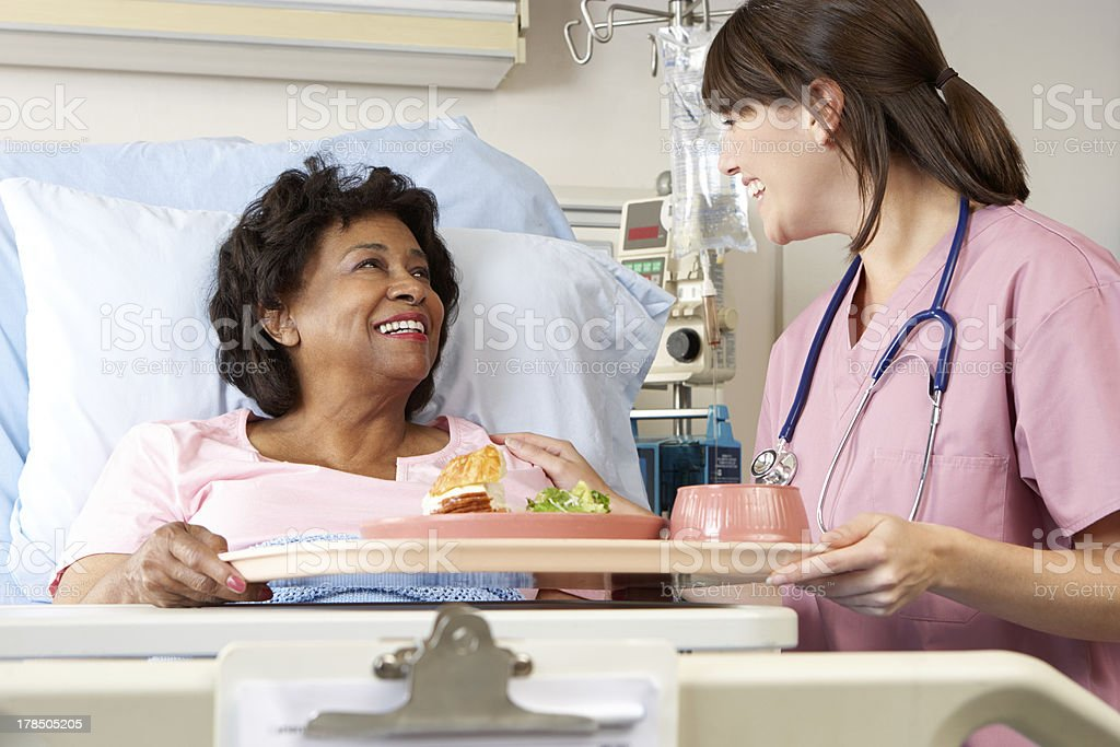 Nurse Serving Senior Patient Meal In Hospital Bed stock photo