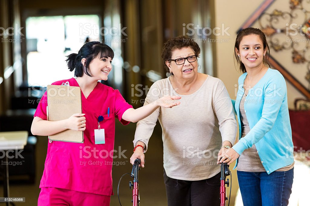 Nurse shows senior woman around in assisted living facility stock photo