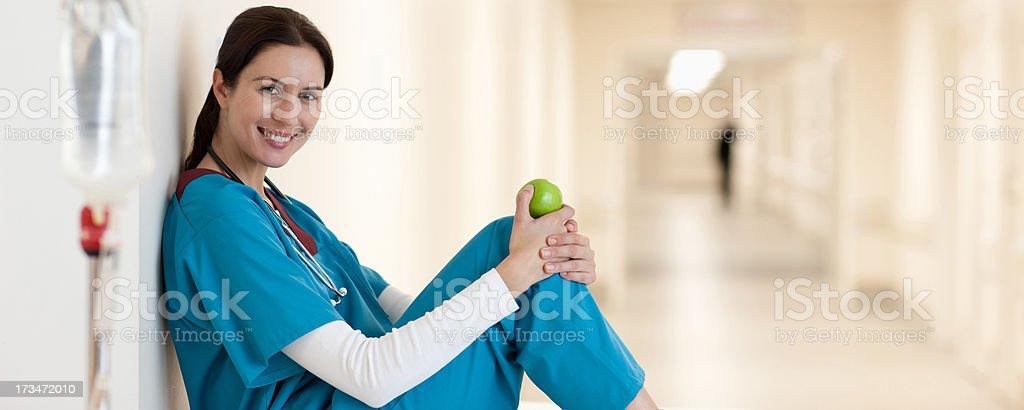 Nurse sitting with apple in hospital corridor stock photo