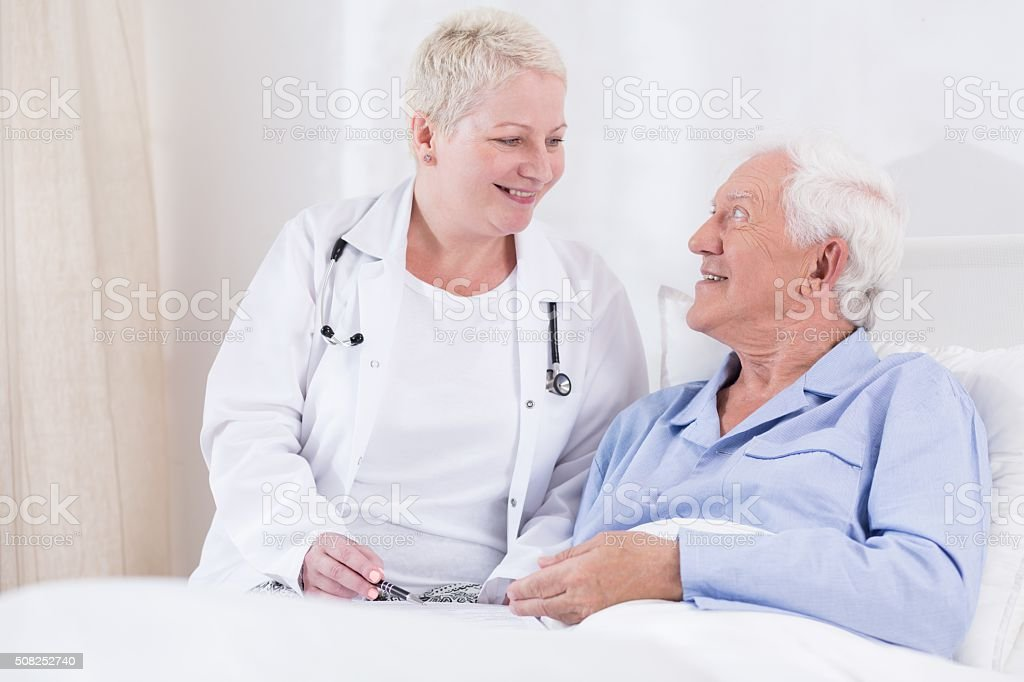 Nurse smiling to her senior patient stock photo