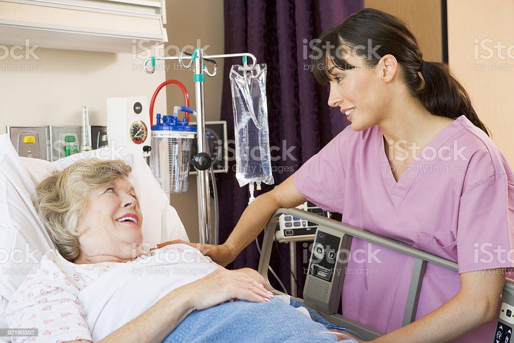 Nurse softly talking to an elderly woman stock photo