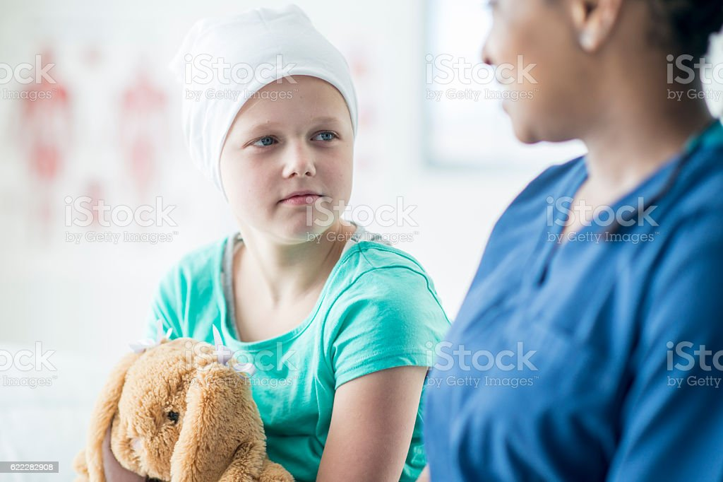 Nurse Spending Time with a Child with Cancer stock photo