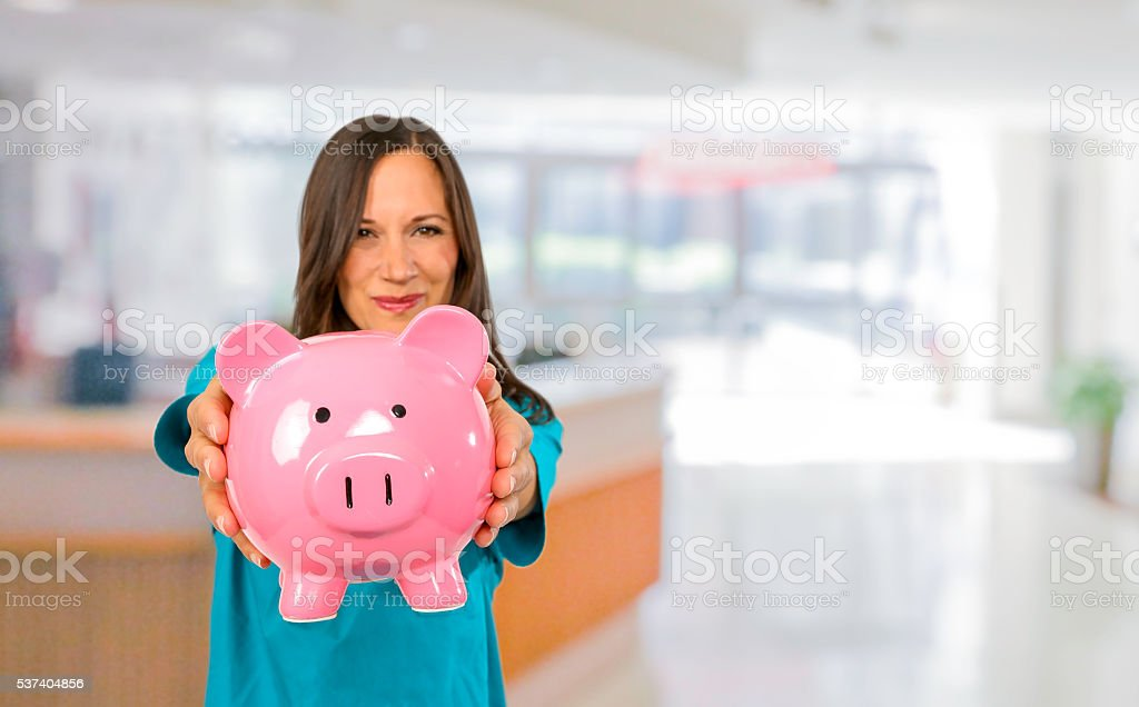 Nurse standing in hospital with piggy bank stock photo