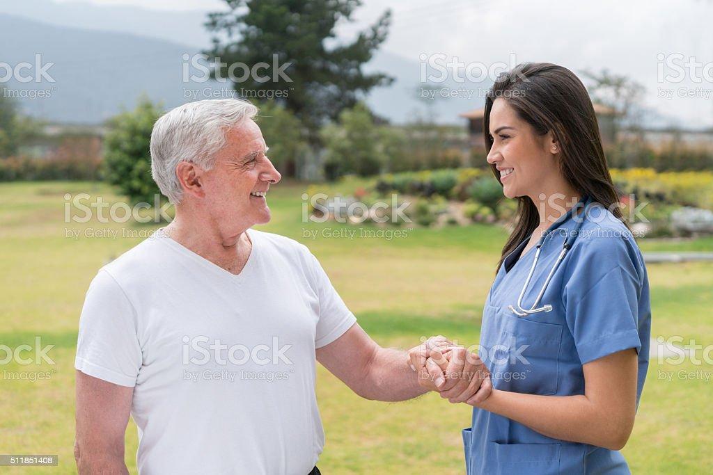 Nurse taking care of a senior man stock photo