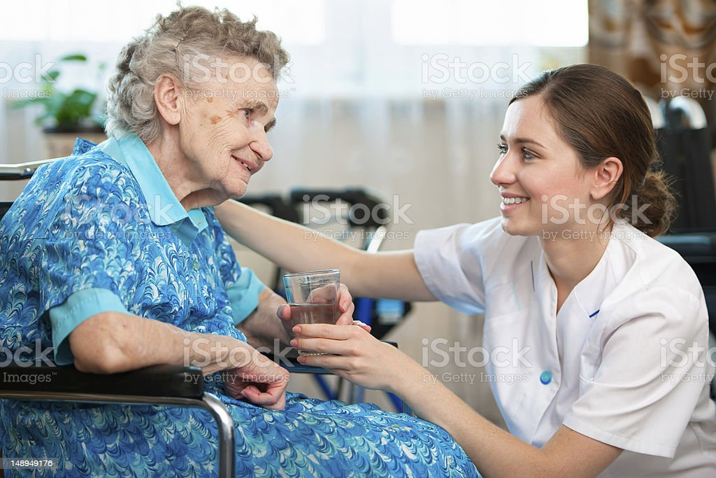 A nurse taking care of an elderly woman at home royalty-free stock photo