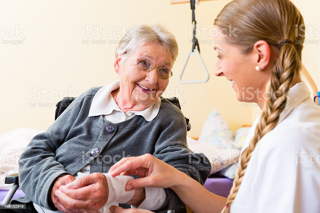 Nurse taking care of senior woman in retirement home stock photo