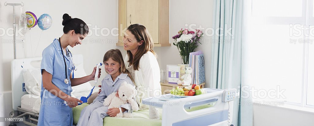 Nurse taking girls temperature with otoscope in hospital royalty-free stock photo