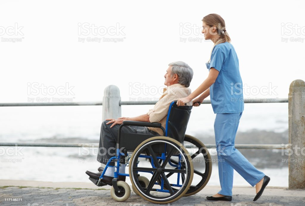 Nurse taking patient for a stroll on pier royalty-free stock photo