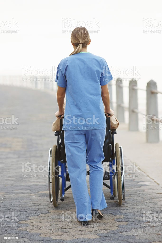 Nurse taking patient for a stroll royalty-free stock photo