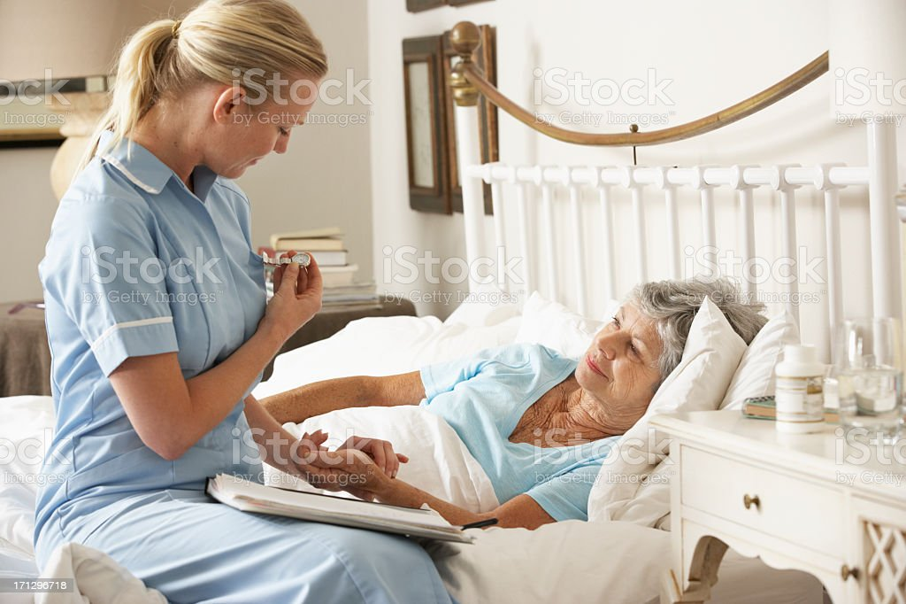 Nurse Taking Pulse Of Senior Patient  In Bed stock photo