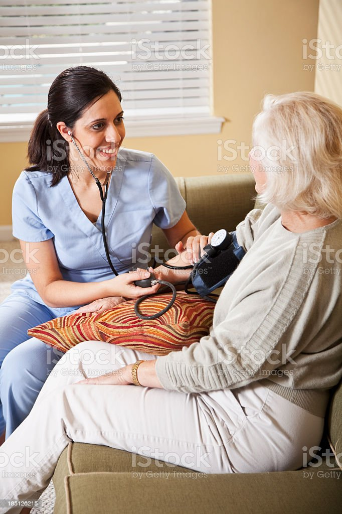 Nurse taking senior woman's blood pressure royalty-free stock photo