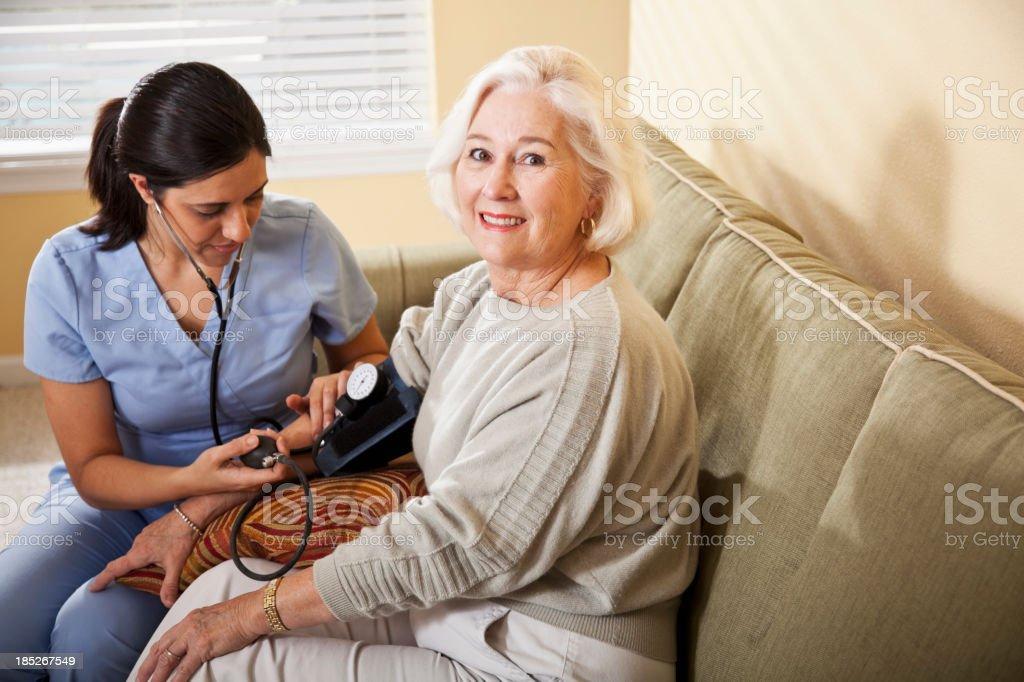 Nurse taking senior woman's blood pressure stock photo