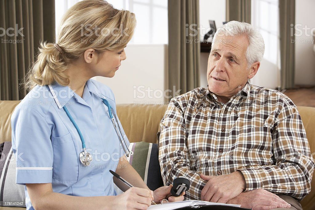 A nurse talking to a senior man and taking notes royalty-free stock photo
