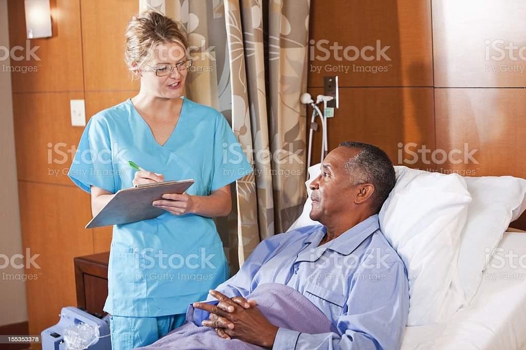 Nurse talking with patient in hospital bed stock photo