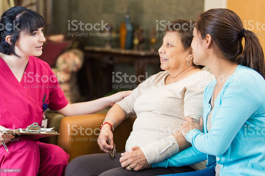 Nurse talking with senior patient about diagnosis stock photo