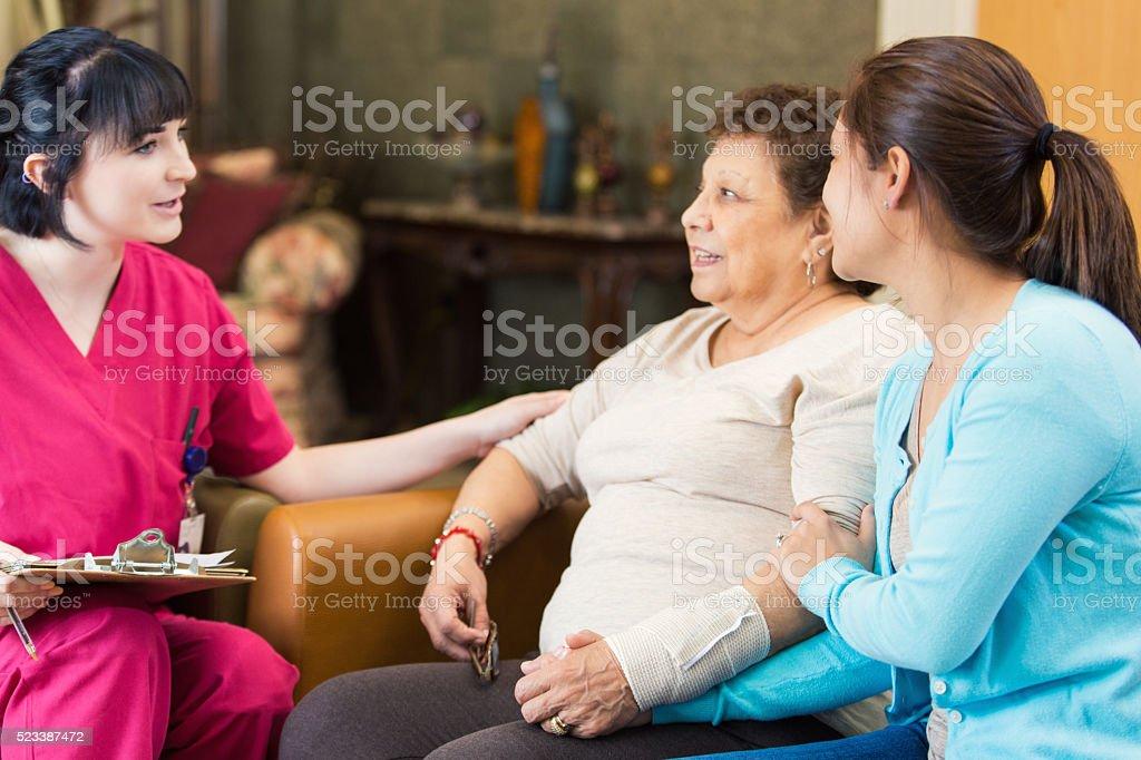 Nurse talking with senior patient about diagnosis stock photo