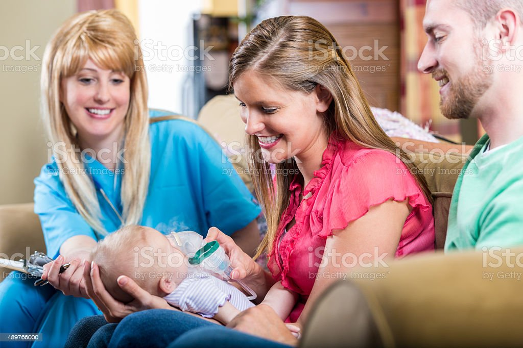 Nurse teaching parents how to give newborn baby breathing treatment stock photo
