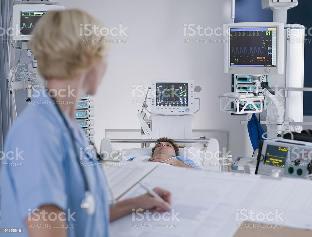 Nurse tending patient in intensive care stock photo