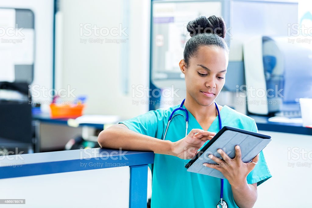 Nurse updating digital patient charts in modern emergency room stock photo