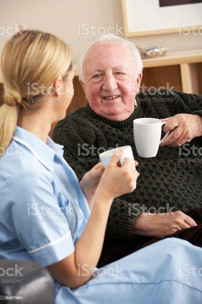 Nurse visiting senior man at home royalty-free stock photo