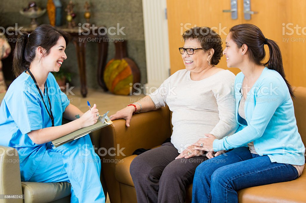 Nurse visits with senior patient and her caregiver stock photo