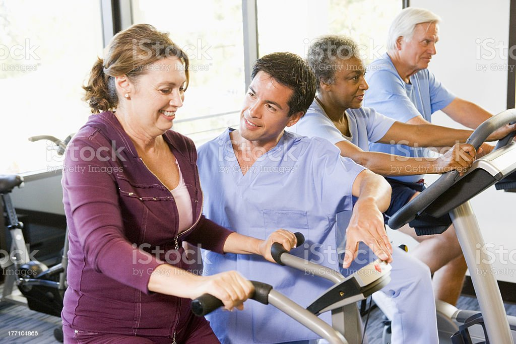 Nurse With Patient In Rehabilitation Using Exercise Machine stock photo