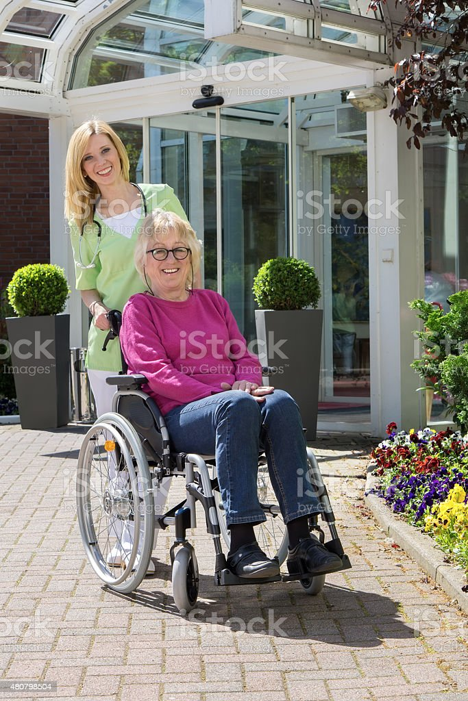 Nurse with Senior Woman in Wheelchair Outdoors. stock photo