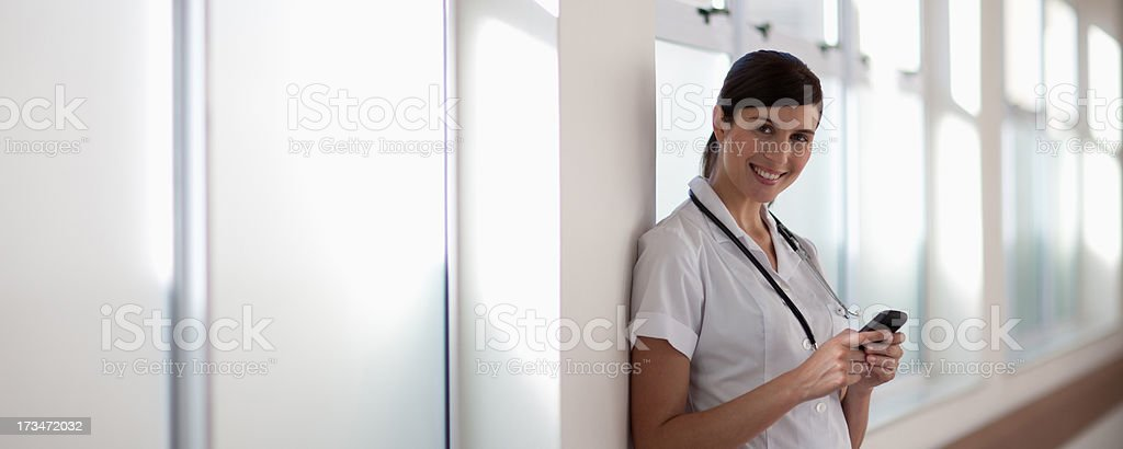 Nurse with text phone in hospital corridor stock photo