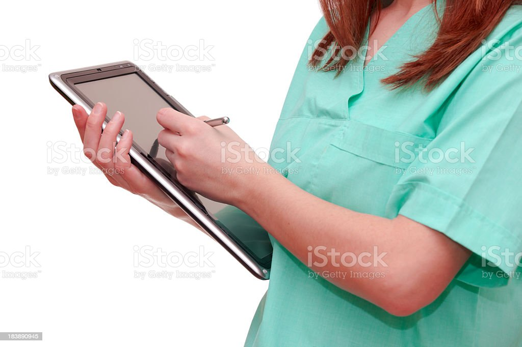 Nurse writing on tablet in green uniform stock photo