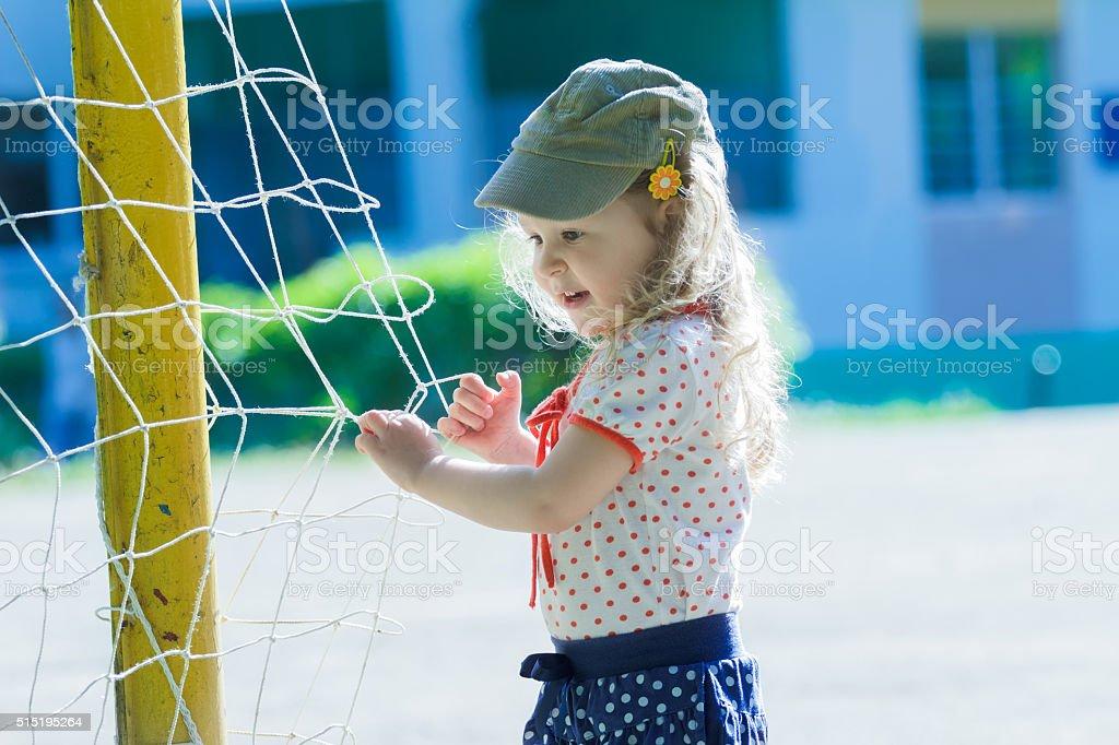 Nursery school girl playing near football goal net with goalposts stock photo