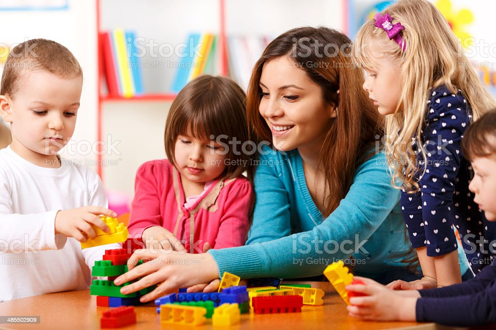 Nursery teacher and preschoolers playing with building blocks stock photo
