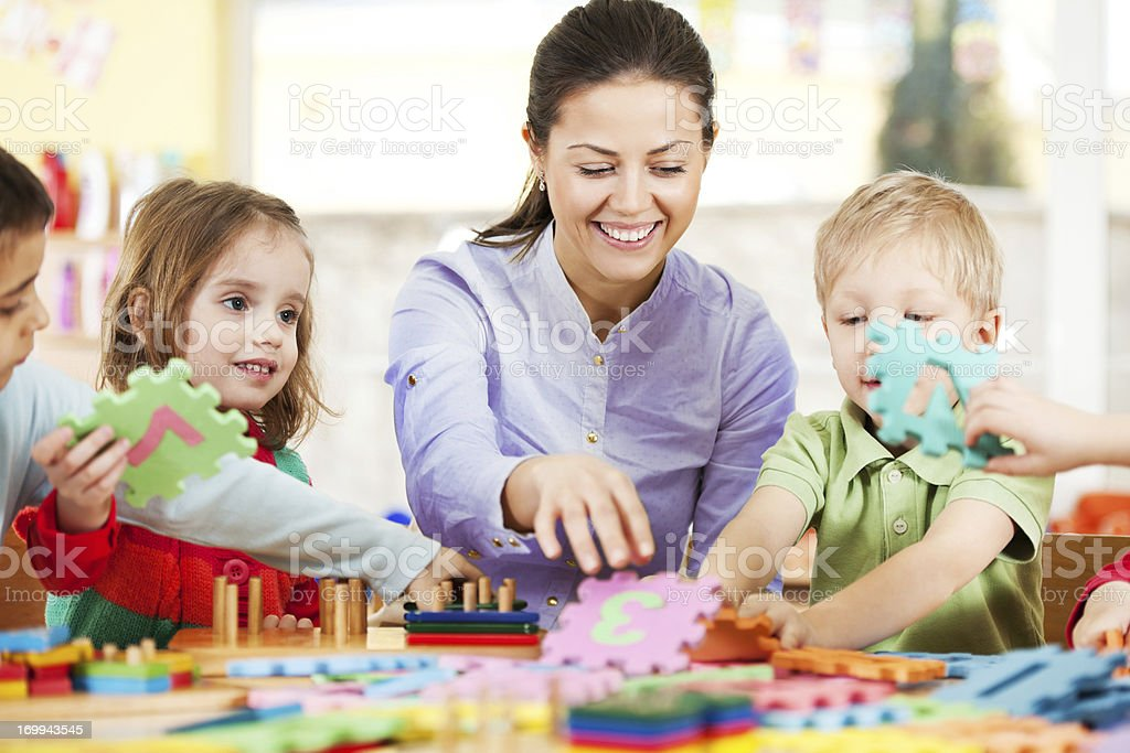 Nursery teacher playing with the kids. stock photo