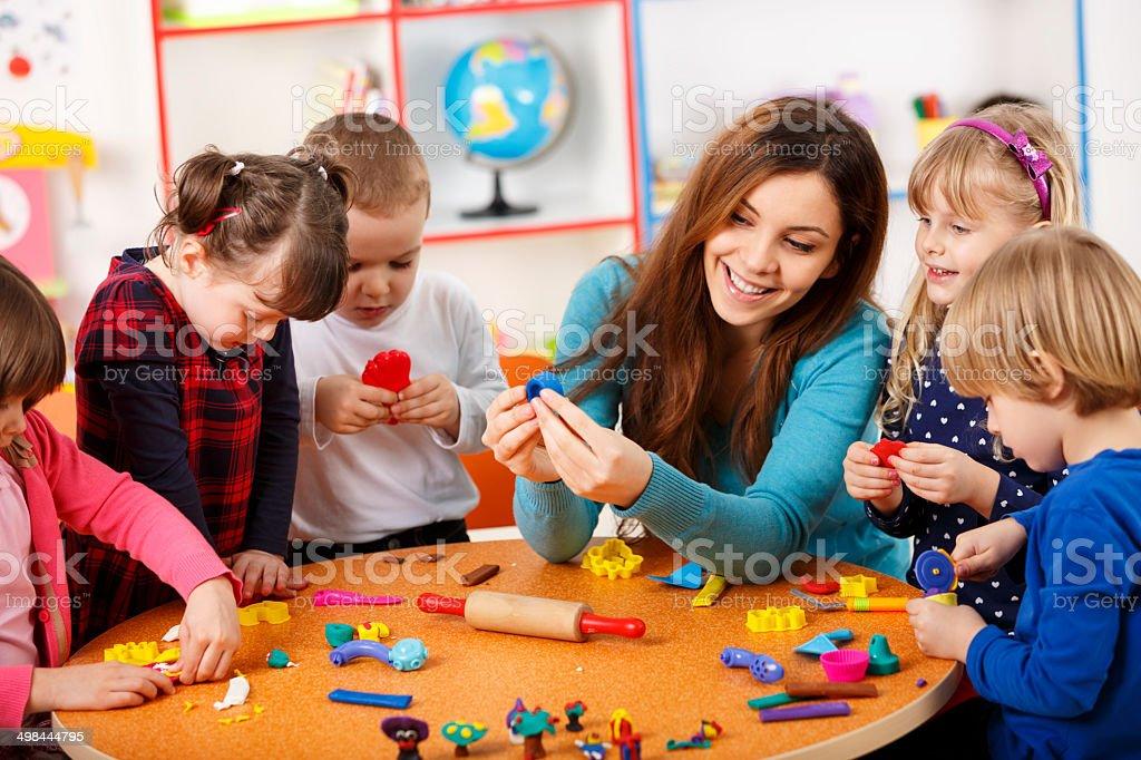 Nursery teacher playing with the kids stock photo